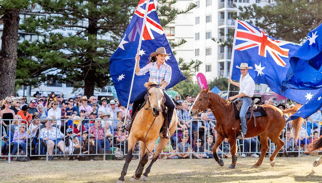 Woman holding Australian flag while riding horse at Groundwater Country Music Festival